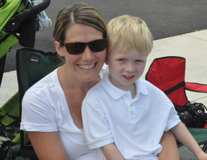 Elias Berger, age 5 of Franklin, cuddles up with mom Debbie to watch the parade.