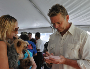 John Schneider signs an item for a fan, and her dog.
