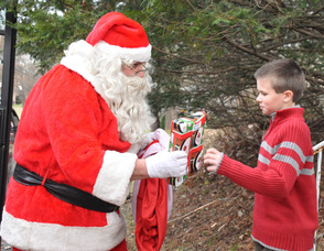 Edward Holder, age 10, receives his gift from Santa.
