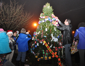 Residents place ornaments on the tree.