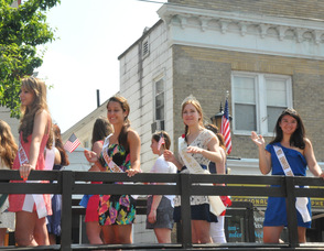 A bevy of beauty queens waves from atop one of the military vehicles.