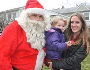 Santa greets Jillian Ackerman, age 3, with her mom, and gives her some candy.