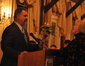 Barbara Garths receives flowers from Scott Longcor, Vice President of the SCNJSHOF, for her service as president.
