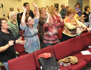 Members of the crowd raising their hands during praise and worship.