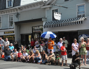Locals sit and wave flags while watching the parade.