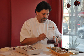 Chef George Mandakas of Innova Cuisine, prepares oysters on the half shell with pomegranate and pink peppercorn pearls.