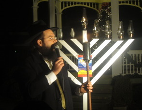 Rabbi Shalom Lubin, the director of the Chabad Jewish Center of Madison lighting the menorah
