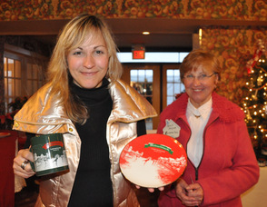 Sandra Meyer (left) holds up a plate and mug commissioned for the German Christmas Market, with mother Karin Meyer (right) in the background.