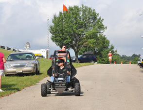 Samuel Burlum leads the race in a Sidewinder ATV with Brian Thomas, and Catherine Stone, running behind.