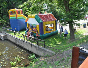 Children bounce in the bounce houses adjacent to the river..