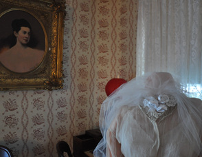 A portrait of Britta M. (Cooper) Carnahan overlooks her wedding gown from 1871 inside the museum.