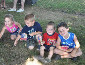 Green Township children grab some shade during the parade: Lily Garafano, age 2; Lucas Garafano, age 4, Mason Garafano, age 2; and Jack Jacinto, age 5.