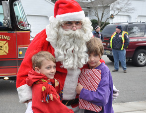 Santa steals a hug from brother Damon, and Ronan Postance, ages 10, and 7.