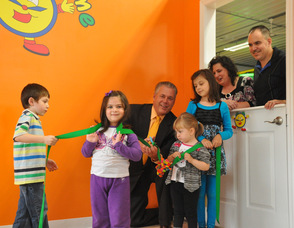 Mayor Michael Lensak at the ribbon cutting for Chuckle Time, with children Ryan Hudock, age 6, of Newton; Brianna Kash, age 3, of Byram, Samantha Hudock, age 3, of Newton; and Gabrielle Derewsky, age 7, of South Plainfield, N.J. Dawn and George Hudock, owners, overlook the ribbon cutting from the window.
