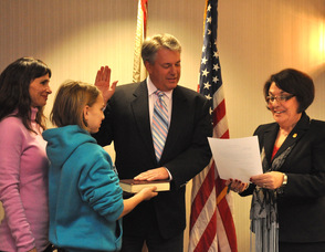 Samantha Lensak holds the Bible for her father Michael Lensak, as he is sworn in by administrator/clerk Vita Thompson, for another term as committee member. Wife Lisa is also pictured. Lensak was sworn in twice during the evening, also for deputy mayor.