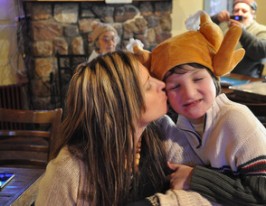 Erica Alcock-Phillips plants a kiss on the cheek of son, Lennon Alcock, age 8, who sported a turkey hat.