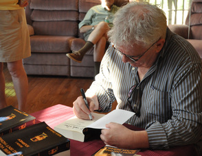 Max Zimmer signs a book at the book signing event held in his honor.