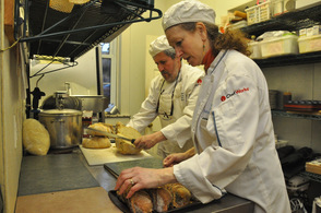Bobolink Dairy owners and chefs Nina and Jonathan White slice freshly baked bread with garlic.