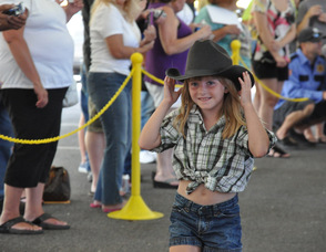 "A ""Little Miss Daisy Duke"" holds onto her hat."