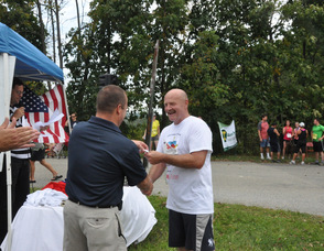 Undersheriff Keith Armstrong receives his ribbon from Sheriff Michael Strada.