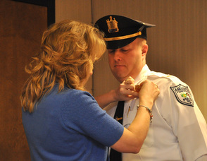 Debbie Danielson pins on the lieutenant's badge for her husband, Eric Danielson, newly sworn in Andover Township Police Lieutenant.