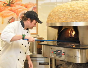 Billy Ganue places a pizza in the special Vesuvius Ash Brick oven, that can cook at temperatures of 900 degrees Fahrenheit.