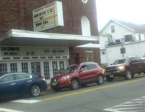 Cars wait outside of The Newton Theatre, while gridlock prevailed at the intersection. Some drivers impatiently made hand gestures at other drivers in front of them. The marquee of The Newton Theatre, was visibly also missing some letters, courtesy of Hurricane Sandy.