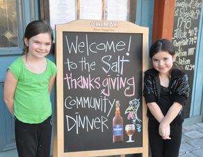 Milla and Tasha Hornung, ages 8, and 5, flank the community dinner welcome sign.