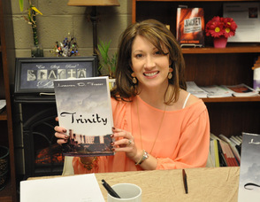 "Lauren D. Fraser with her book, ""Trinity."""