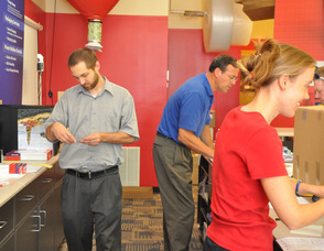 Steve Geary, Dan Thomas, and Wendy Asplund handling various facets of the business from behind the counter.