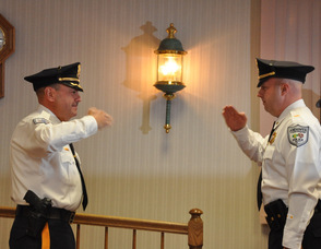 Andover Township Police Chief Gil Taglialatela (left), and Lieutenant Eric Danielson (right) salute each other in unison, after Danielson has taken his oath.