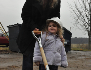 Three-year-old Brianna Strada sports a hard hat and poses with a shovel at the groundbreaking site, along with her mother, Kim.