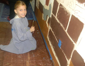 A student painting the mural